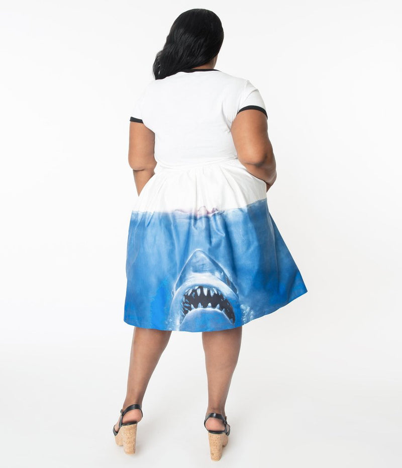 This is a Unique Vintage Jaws movie poster skirt and the model has dark hair, red shoes and the skirt is white at the top, blue water on the bottom and a shark coming up to eat a swimmer, on the back, on a plus size model.
