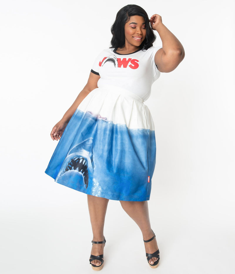 This is a Unique Vintage Jaws movie poster skirt and the model has dark hair, red shoes and the skirt is white at the top, blue water on the bottom and a shark coming up to eat a swimmer, on a plus size model.