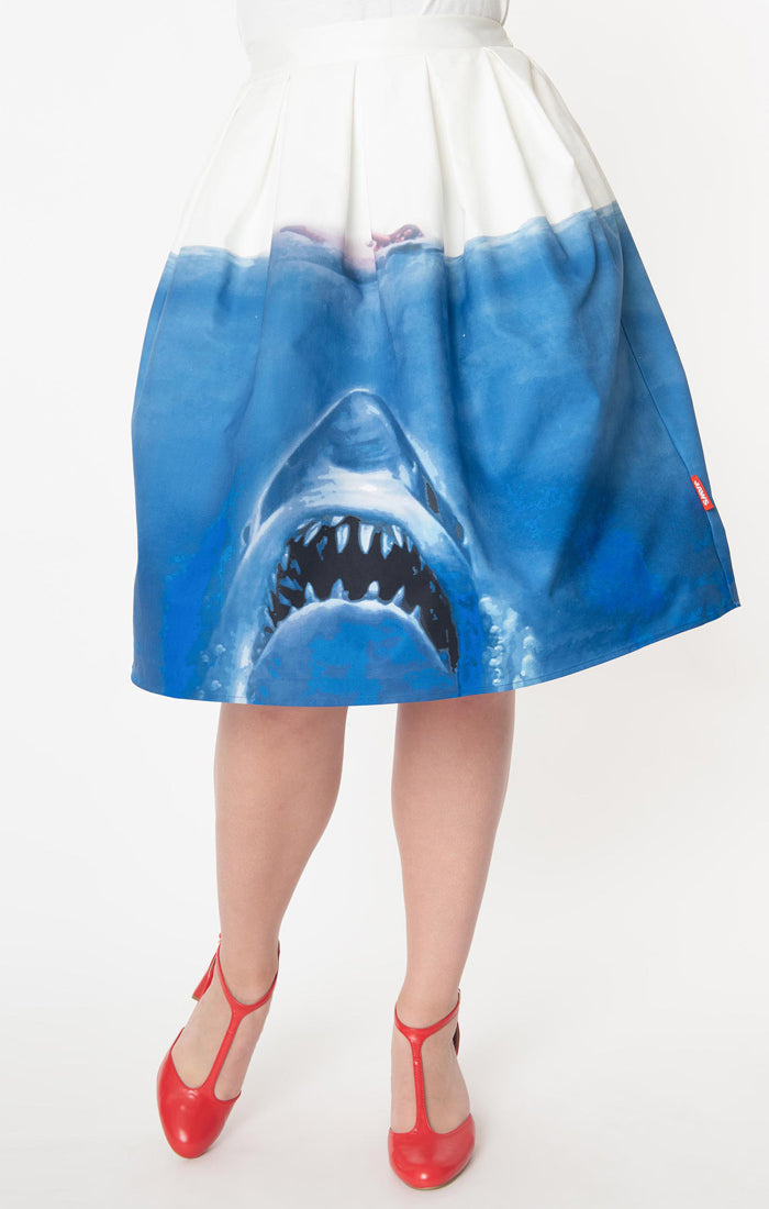 This is a Unique Vintage Jaws movie poster skirt and the skirt is white at the top, blue water on the bottom and a shark coming up to eat a swimmer.