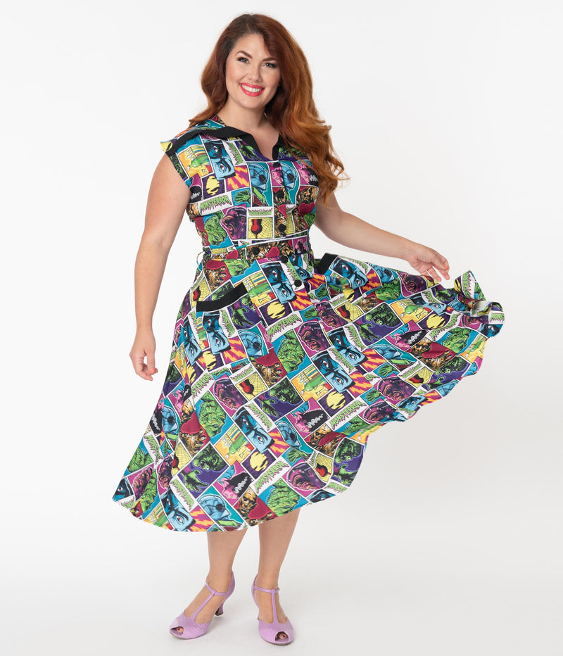 This is a Universal Monsters Hedda dress from Unique Vintage and it has Creature From the Black Lagoon, Frankenstein, Dracula, Mummy, Bride and Wolfman and has a black collar and two pockets on a plus size model, who is wearing pink shoes.