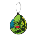 This is a Universal Monsters Creature From the Black Lagoon air freshener by Trick Or Treat and he has green skin and gills and scales with red lips and is in front of a blue circle and fish, with a plastic hanger.
