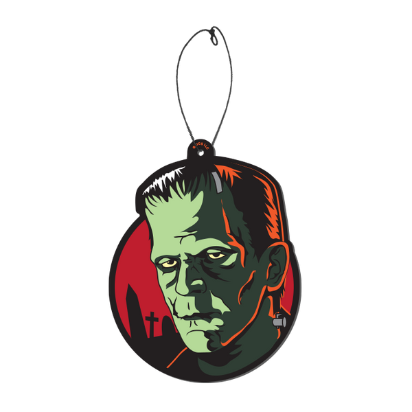 This is a Universal Monsters Frankenstein air freshener by Trick Or Treat and he has green skin, black hair and is in front of a red circle with headstones, with a plastic hanger.