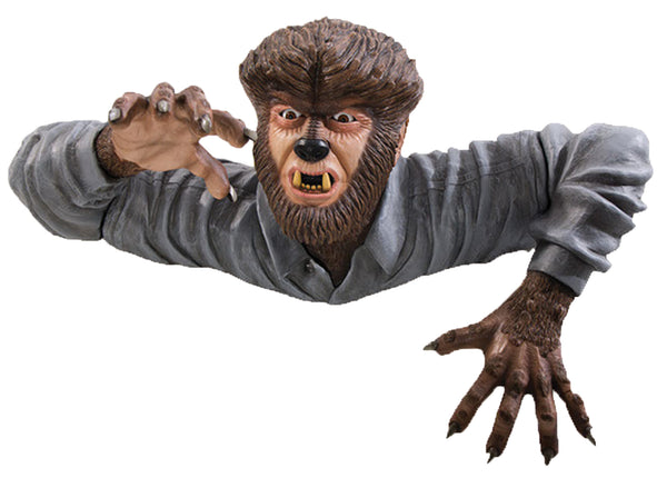Universal Monsters Wolfman grave walker decor is crawling out of the ground in a long sleeve shirt with furry arms and face.