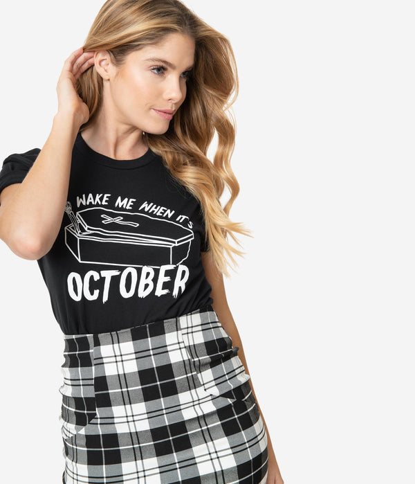 This is a Unique Vintage wake me when it's October black unisex t-shirt, with white letters and the model has a black and white skirt on, with the shirt tucked in.