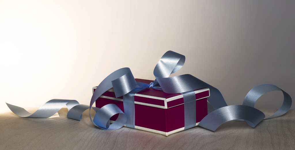 A closed red gift box with white trimmings tied using a silvery blue ribbon.  The gift is places on the floor in the room right under the warm lighting.