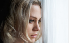 A girl looking out the window showing depression.