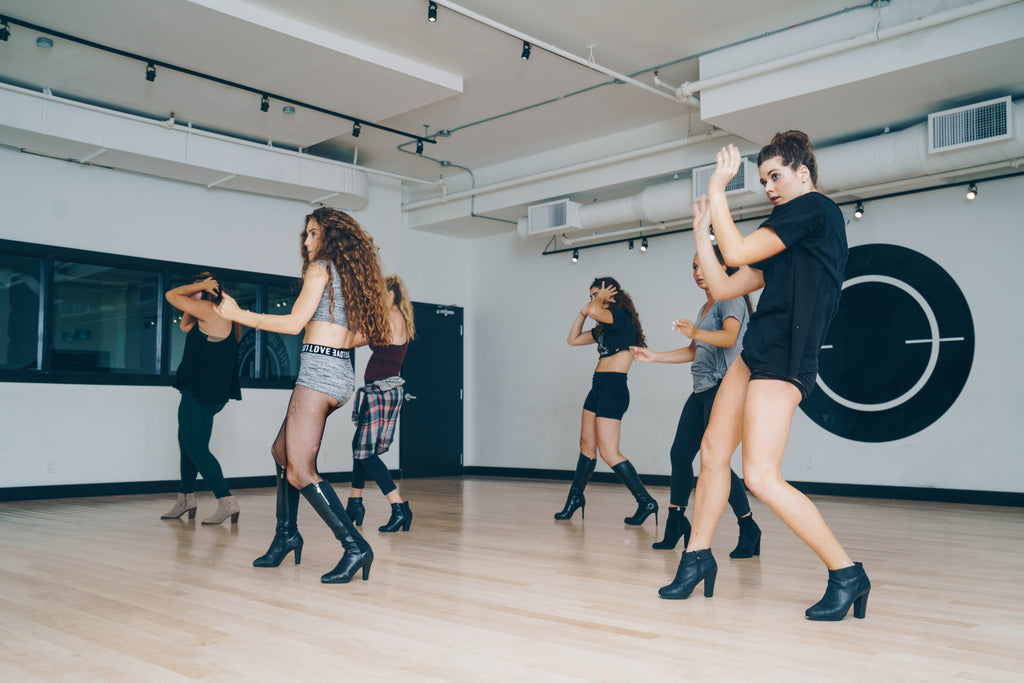 A group of young dance enthusiasts participating in a dance studio session.  Dancing to the music beat shows their happy and uplifting attitude.