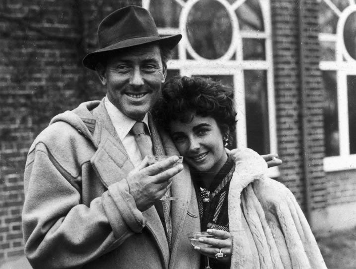Actor Michael Wilding wears the duffle coat stood with film star wife, Elizabeth Taylor.
