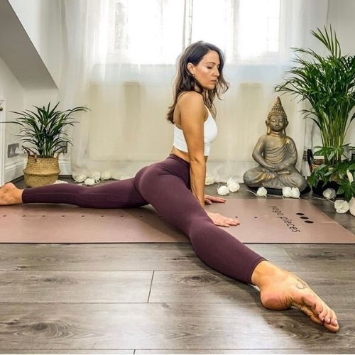 Yoga model stretched out with wide leg splits wearing Iono mogul red leggings and white Stellar bra.
