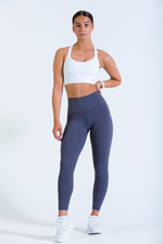 Female model wearing Serenity Bra in white with Aurora Luxe leggings