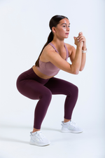 Female model wearing Women's Iono high waist leggings in Mogao Red and Stellar Bra performing a squat