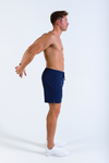Male model wearing Mens Vitesse lightweight above knee shorts in Tungsten Blue with drawstring and white trainers