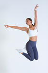 Female model wearing Serenity Bra in white with Aurora Luxe leggings jumping