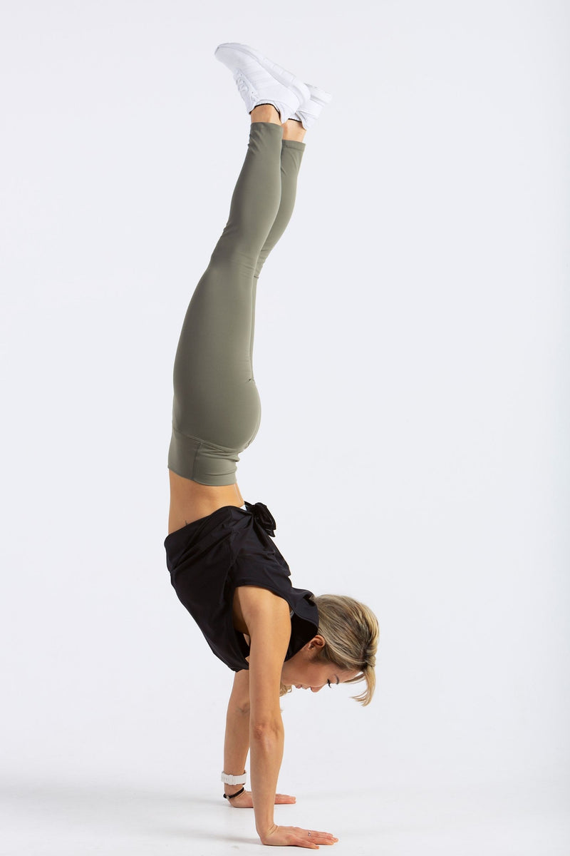 Aeon Vie Arise Tank in Black with Define leggings in Olive performing a handstand