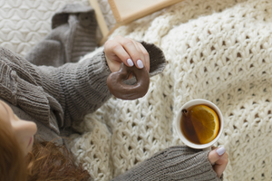 Person holding a cup of tea and a sugary snack keeping warm under a blanket