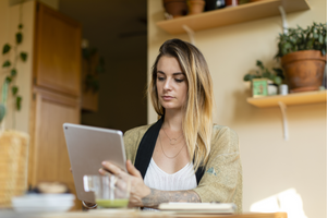 Woman shopping for groceries on her tablet, while working from home