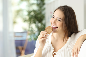 Woman smiling eating a Bellycrush oatmeal hemp cookie
