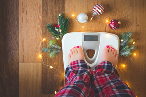 Person wearing jammies checking their holiday weight on a scale with Christmas decorations surrounding them