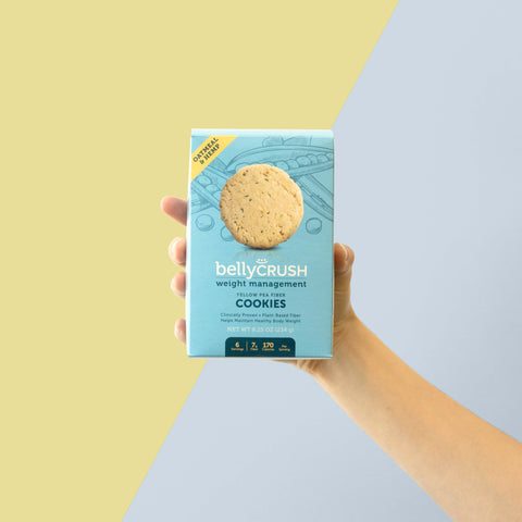 A person holding a light blue box of oat meal hemp weight management cookies