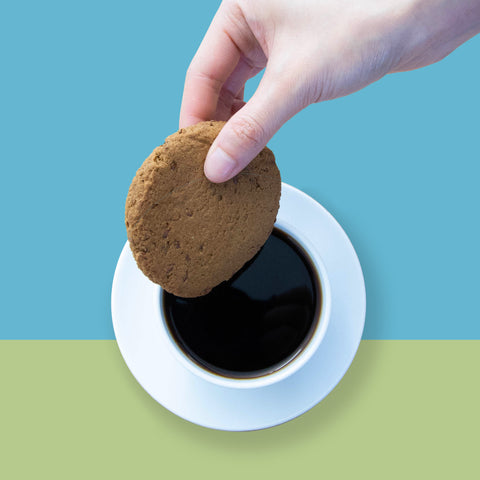 someone dunking a yellow pea fibre ginger flax cookie into a cup of coffee