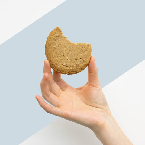 a person holding a ginger cookie that's been bitten