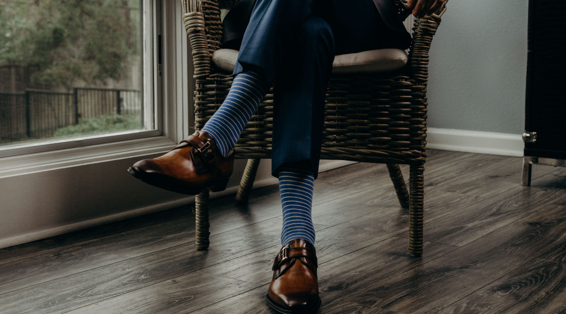 Man crossing his legs wearing blue and white striped men's dress socks with a navy suit and brown shoes