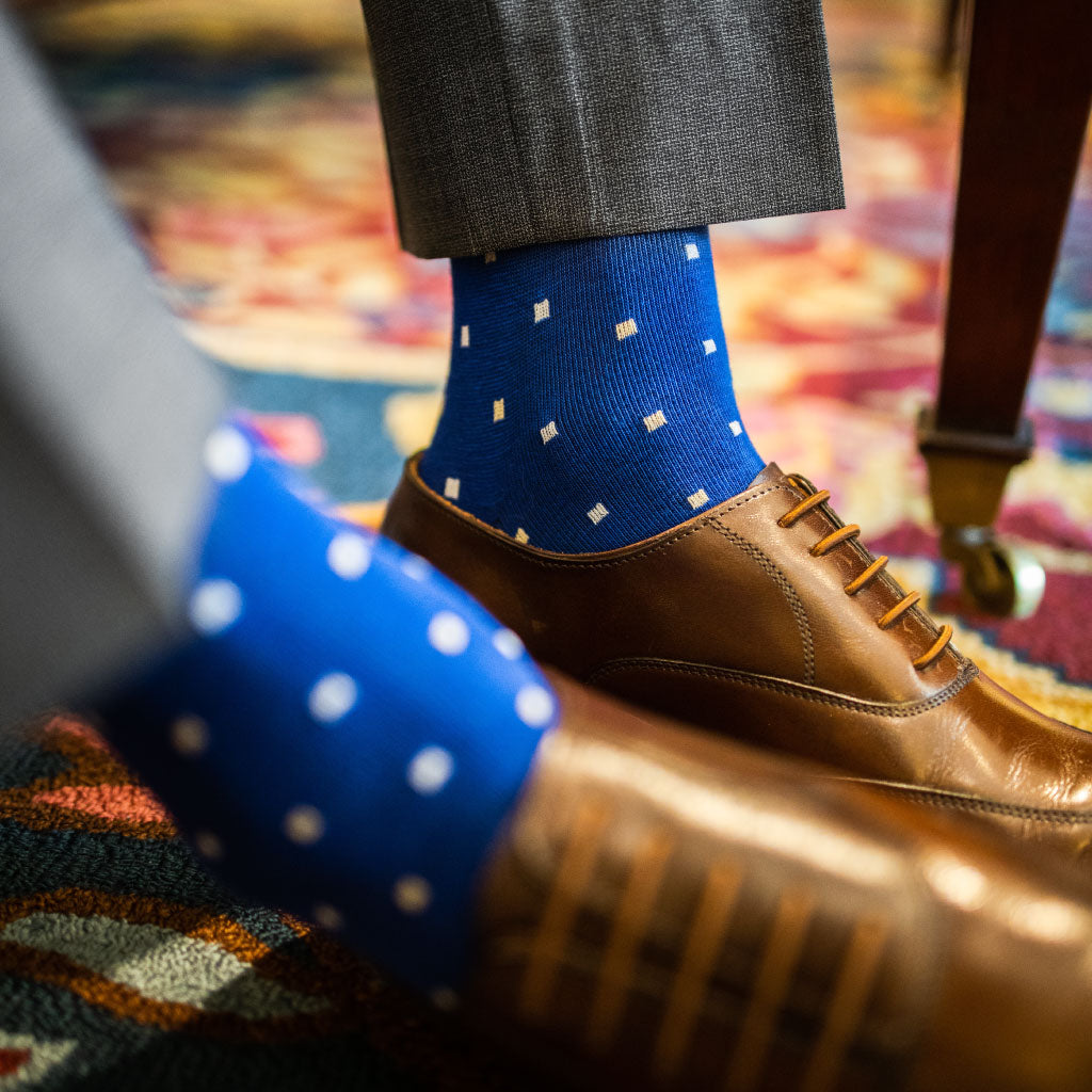 man wearing blue men's dress socks with white and tan polka dots pattern, grey trousers, and brown shoes