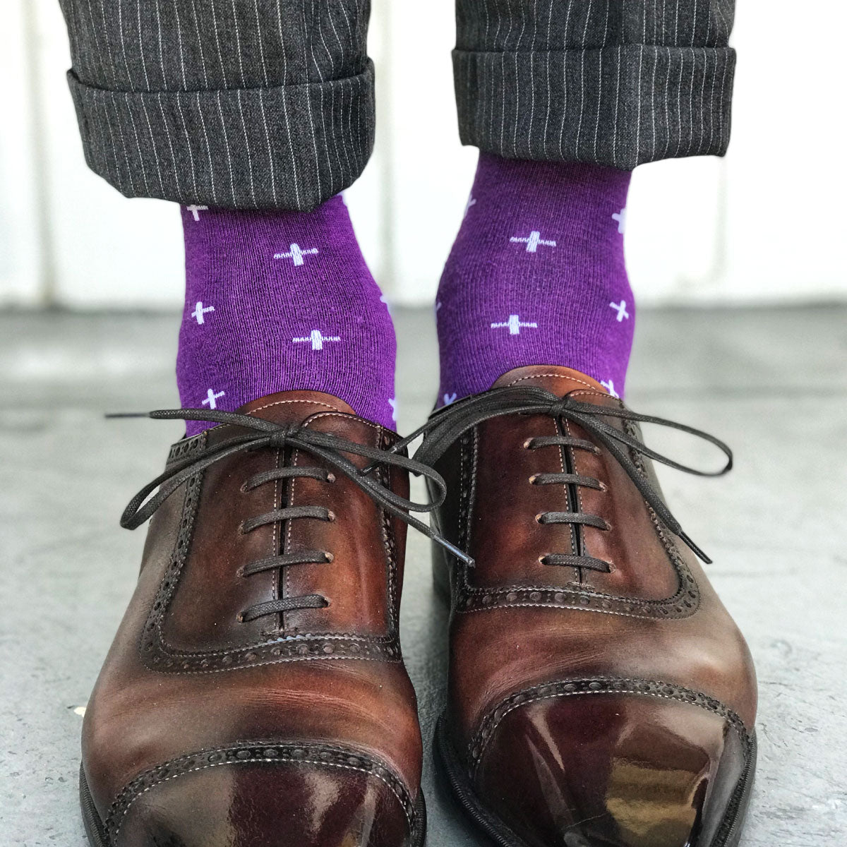 Guy wearing purple socks with grey slacks and brown shoes
