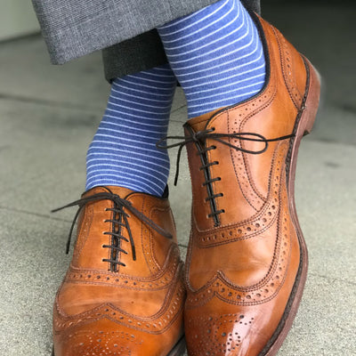 Man wearing blue striped socks and brown shoes