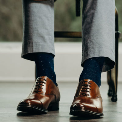 Man wearing blue socks with grey pants