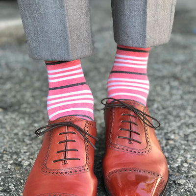 guy wearing coral striped socks and grey pants