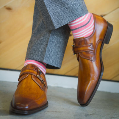 Man wearing coral striped socks and grey pants