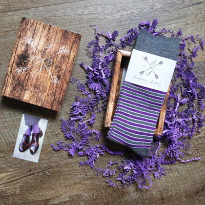 A pair of purple, grey, and white striped dress socks and gift box