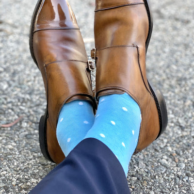 Man wearing navy slacks, light blue socks with white polka dots, and tan double monks trap shoes
