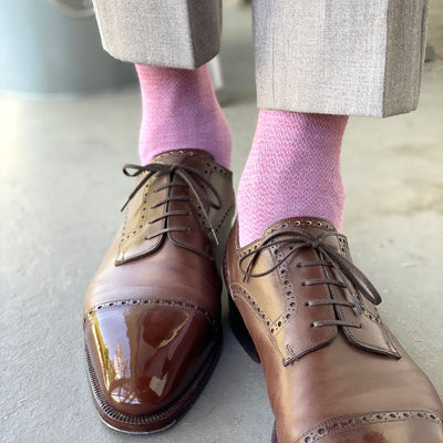 Man wearing light grey slacks, pink socks, and brown shoes.