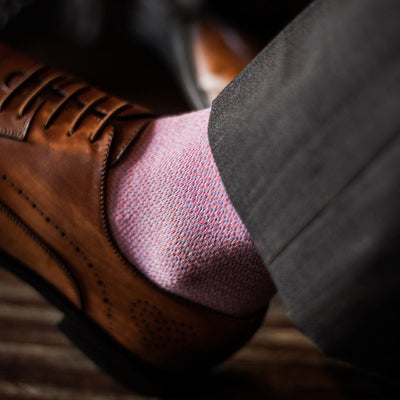 A close up shot of a man wearing tan dress shoes, salmon colored socks, and grey trousers