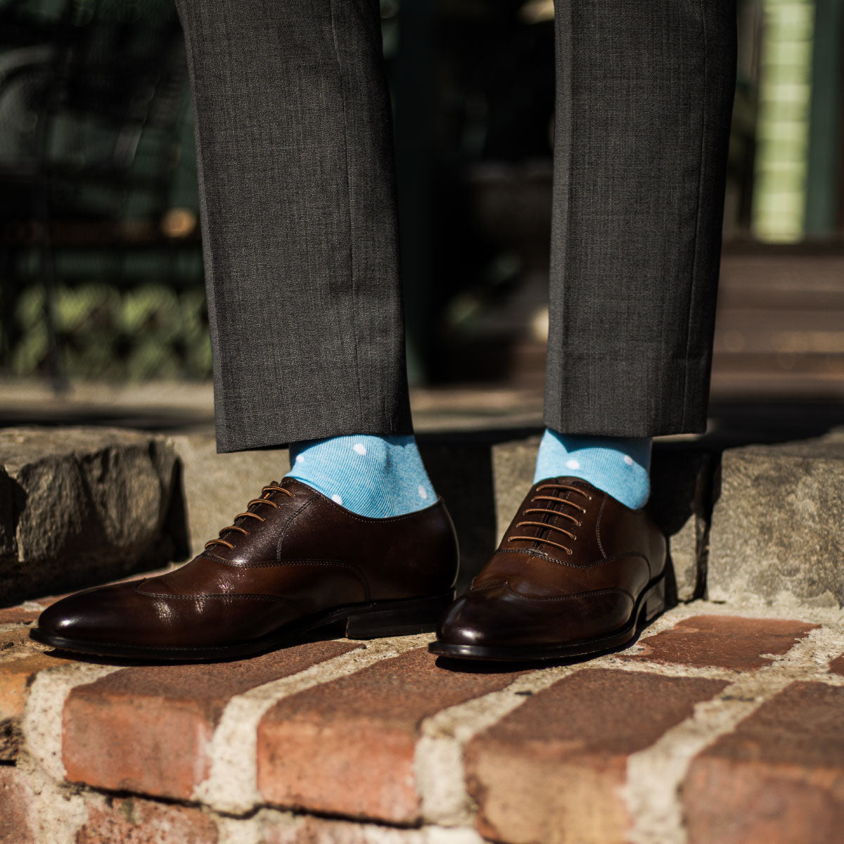 Man wearing charcoal grey slacks, baby blue and white polka dot socks, and brown dress shoes