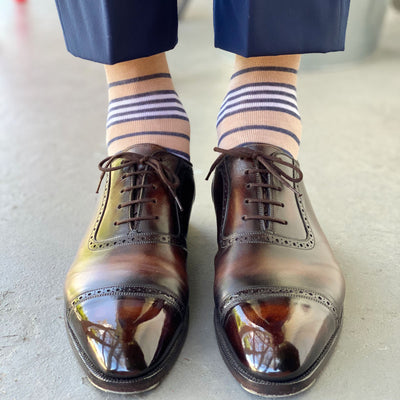 Guy wearing tan, white, and blue striped socks with navy slacks and brown shoes