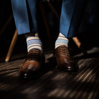 Man sitting and wearing blue trousers with tan, navy blue, and white striped dress socks and dark brown dress shoes