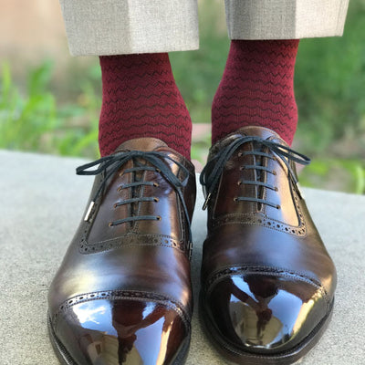 A man wearing burgundy socks and brown shoes