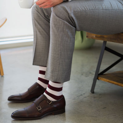 man wearing crimson striped socks and grey pants