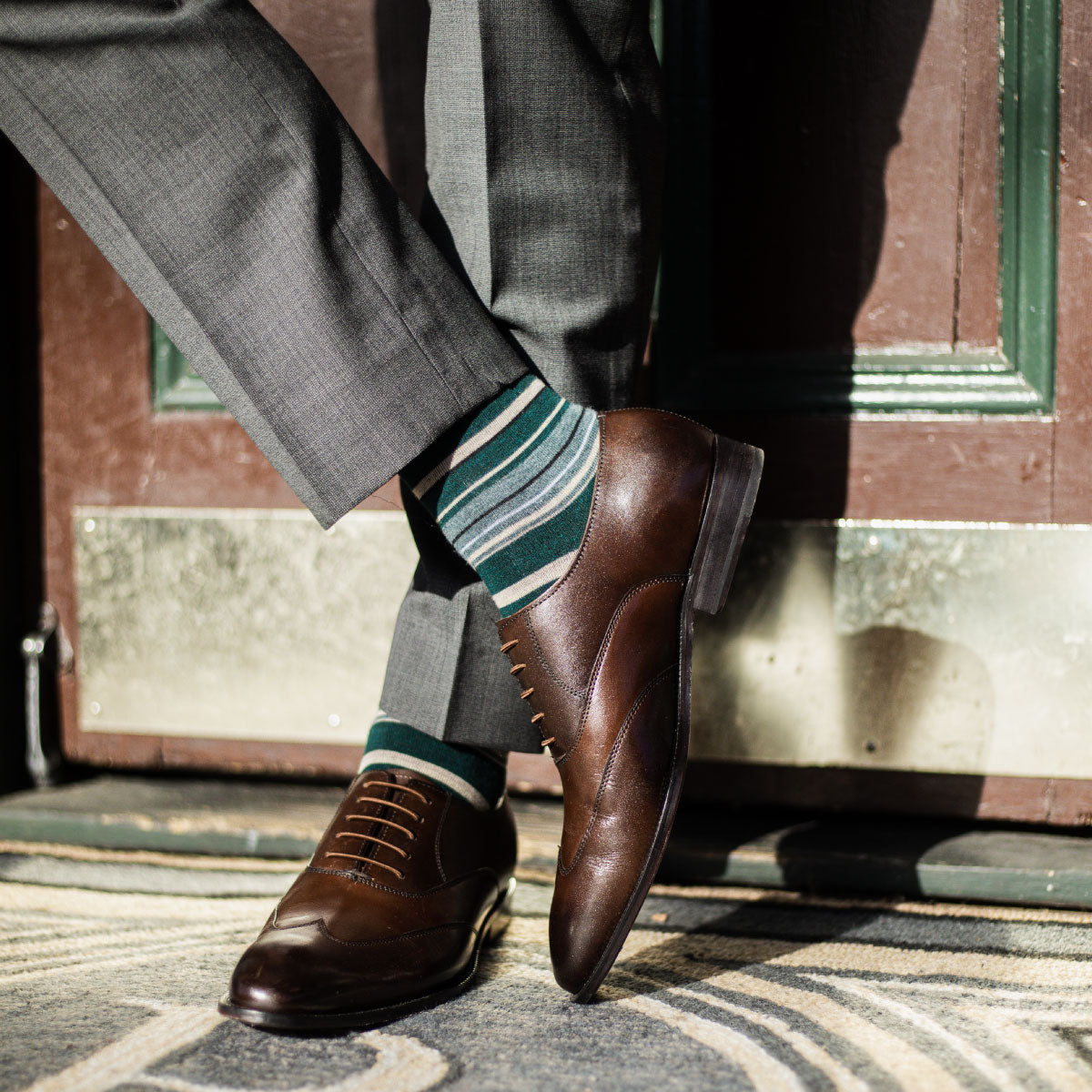 man wearing green, taupe, and tan striped dress socks