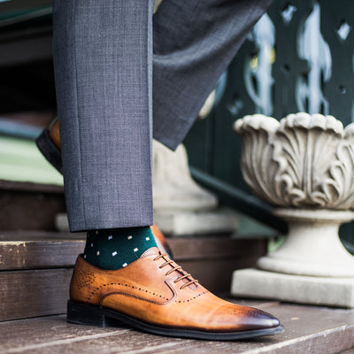 guy wearing grey slacks, green socks, with tan dress shoes