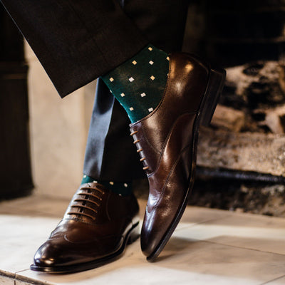 guy wearing charcoal grey slacks, green socks, with dark brown dress shoes