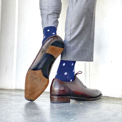 Man wearing grey pants, navy blue socks with white polka dots, and brown dress shoes.