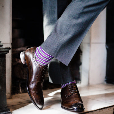 A man wearing purple, grey, and white striped dress socks, brown dress shoes, and grey slacks