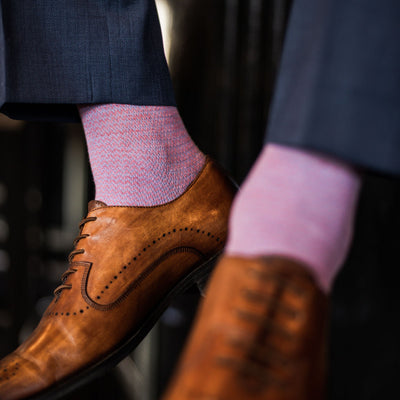 A man wearing blue trousers, pink and blue socks, and tan dress shoes.
