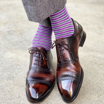 A man wearing purple, grey, and white striped dress socks and brown dress shoes