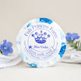 round blue violet goat milk soap on natural background with flowers