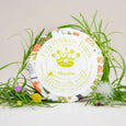 round meadow goat milk soap on natural background with grass and flower props